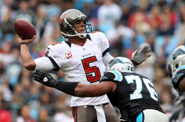 CHARLOTTE, NC - NOVEMBER 18:   Greg Hardy #76 of the Carolina Panthers hits Josh Freeman #5 of the Tampa Bay Buccaneers as he throws a pass during their game at Bank of America Stadium on November 18, 2012 in Charlotte, North Carolina.  (Photo by Streeter Lecka/Getty Images)