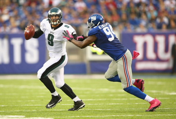EAST RUTHERFORD, NJ - OCTOBER 06:  Nick Foles #9 of the Philadelphia Eagles eludes  Mathias Kiwanuka #94 of the New York Giants during their game at MetLife Stadium on October 6, 2013 in East Rutherford, New Jersey.  (Photo by Al Bello/Getty Images)