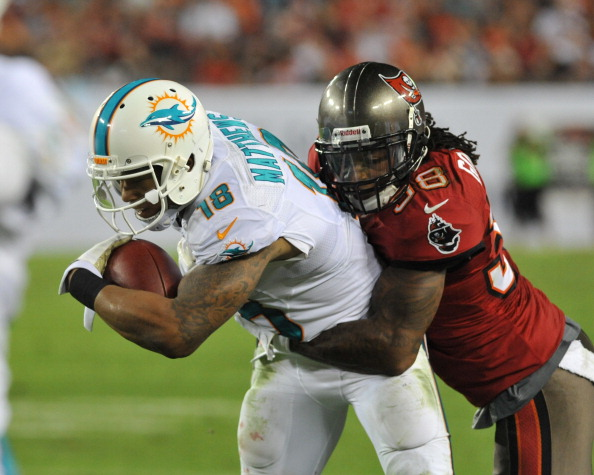 TAMPA, FL - NOVEMBER 11:  Safety Dashon Goldson #38 of the Tampa Bay Buccaneers tackles 2ide receiver Rishard Matthews #18 of the Miami Dolphins November 11, 2013 at Raymond James Stadium in Tampa, Florida. Tampa won 22 - 19.  (Photo by Al Messerschmidt/Getty Images)