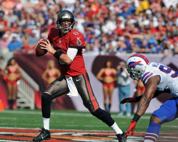 TAMPA, FL - DECEMBER 8: Quarterback Mike Glennon #8 of the Tampa Bay Buccaneers rolls out and tosses a 38-yard touchdown pass in the 1st quarter against the Buffalo Bills December 8, 2013 at Raymond James Stadium in Tampa, Florida. (Photo by Al Messerschmidt/Getty Images)