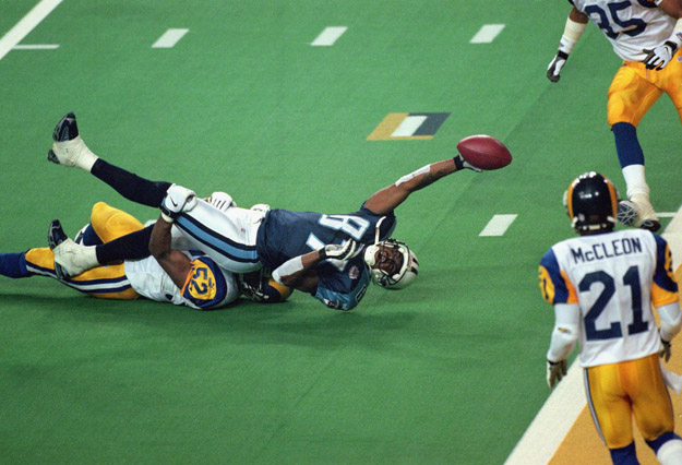 ATLANTA - JANUARY 30:  Kevin Dyson #87 of the Tennessee Titans reaches for the end zone with the ball as Mike Jones #52 of the St. Louis Rams tackles him on the last play of the game during the Super Bowl XXXIV Game at the Georgia Dome on January 30, 2000 in Atlanta, Georgia. The Rams defeated the Titans 23-16.