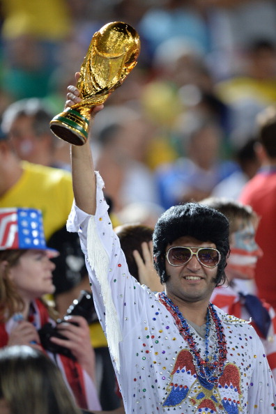 A fan holds a replica of the World Cup trophy during a Group G football match between Ghana and US (credit: CARL DE SOUZA/AFP/Getty Images)