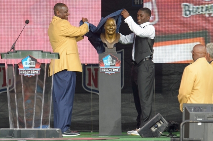 CANTON, OH - AUGUST 2: Former Tampa Buccaneers linebacker Derrick Brooks, left, unveils his bust with his son Decalon Brooks, right, during the NFL Class of 2014 Pro Football Hall of Fame Enshrinement Ceremony at Fawcett Stadium on August 2, 2014 in Canton, Ohio. (Photo by Jason Miller/Getty Images)