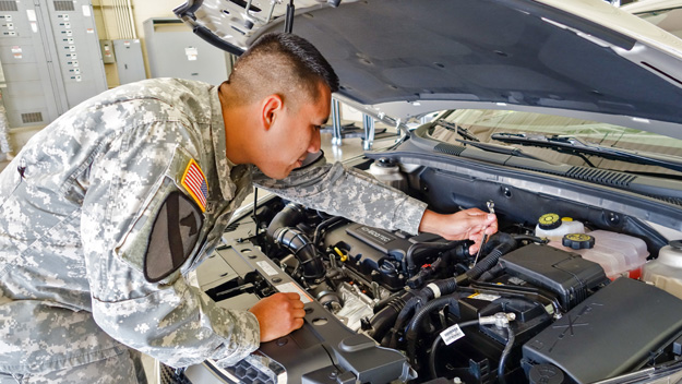 Spc. Javier Mendoza works under the hood of a 2014 GM vehicle at the Raytheon and GM training center at Fort Hood, Texas. Mendoza, a newly GM-certified automotive technician, hopes to find work at a GM dealership in his hometown, Houston, Texas. Photo by Pat McKenna/Raytheon